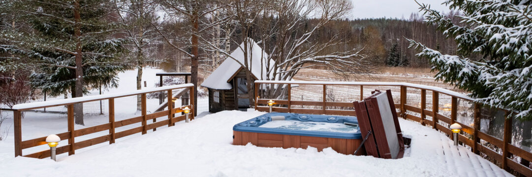 Panorama, outdoor Jacuzzi pool with fresh blue water in winter in Finland. Sauna and Finnish traditions.