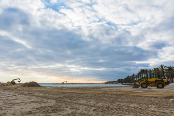 Excavators working on the beach to build a rock pier before the start of the summer season