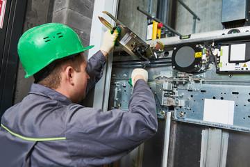 lift machinist adjusting elevator mechanism