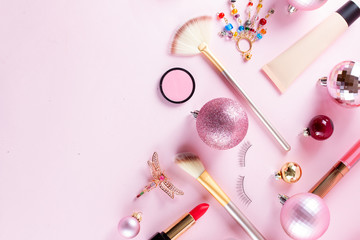Festive make up products close up border on pink background