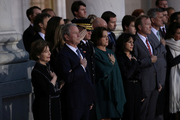 Former First Lady Laura Bush and former President George W. Bush place their hands over their hearts as the casket of former U.S. President George H.W. Bush arrives at the U.S. Capitol in Washington