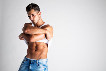 Portrait of a handsome young man with stylish haircut posing in undershirt and jeans. Perfect hair & skin. Close up. Studio shot