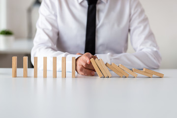 Business executive sitting at his office desk stopping domino effect