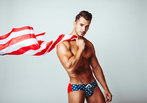 Portrait of handsome young man with stylish haircut in swinwear posing with American flag over gray background. Perfect hair & skin. Close up. Studio shot