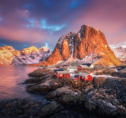 Poster Arctic Hamnoy village on the hill at sunrise. Lofoten islands, Norway. Winter landscape with houses, snowy mountains, sea, colorful sky with clouds. Norwegian traditional red rorbu and snow covered rocks