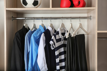 Wardrobe with stylish boy's clothes hanging on rack