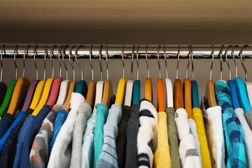 Hangers with teenage clothes on rack in wardrobe, closeup