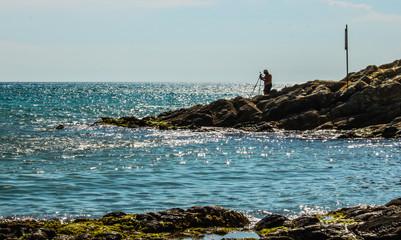 Fisherman on the rocks. Grosseto Tuscany Italy.