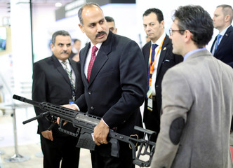 A visitor holds a weapon on the first day of Egypt Defense Expo, showcasing military systems and hardware in Cairo