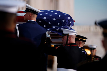 Joint service members of a military casket team carry the casket of former President George H. W. Bush into the US Capitol