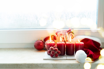 Christmas winter scene with four red burning advent candles on windowsill with frozen window with bokeh lights