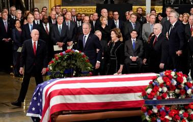 Former President George W. Bush, former first lady Laura Bush, walk past the flag draped casket of former President George H.W. Bush in the Capitol Rotunda
