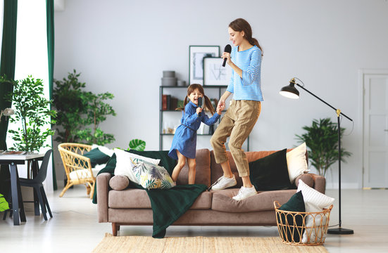 happy family mother and child play at home and sing with combs