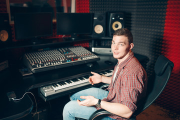 Young stylish man sitting on chair in front of monitor and soundboard. close up photo. copy space. hobby, free time, interest