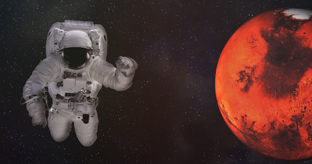Astronaut in outer space with Mars planet of solar system with reflection in helmet. Science fiction wallpaper. Elements of this image were furnished by NASA.