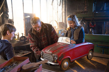 Father and his young childs at workshop, restoring a pedal car