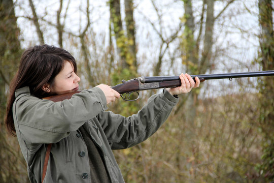 young woman hunter in action, aiming with her vintage shotgun.