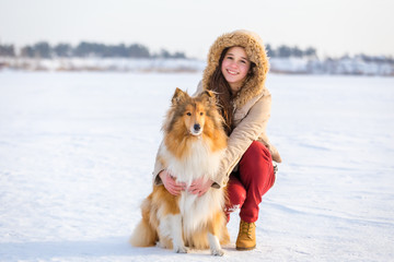 Portrait of girl with collie dog on snowy landscape