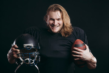 Happy american football player in black sportswear with helmet and ball over black background. People, sport, positive emotions and facial expressions concept