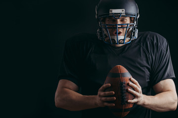Caucasian athlete in american football player uniform and black helmet holding oval ball looking at camera isolated over black background