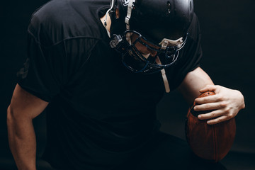 Dramatic portrait of determined American football player equipped with black headgear and protection suit, wearing oval ball isolated on black background