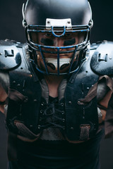 Portrait of athlete - american football player wearing protective shields on bare chest, looking confidently, prepare to tear to pieces everybody who to gets in the way. Team captain.