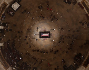People pause to look as Former President George H. W. Bush lies in state in the U.S. Capitol Rotunda Monday