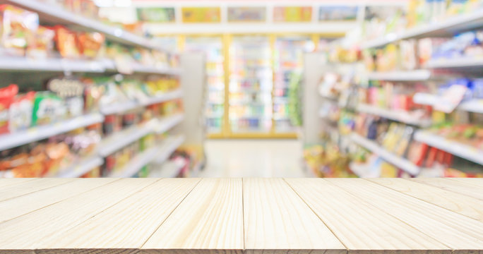 Wood table top with Supermarket convenience store aisle shelves interior blur for background