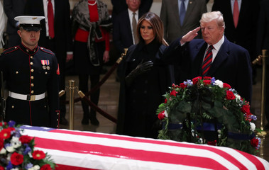 President Donald Trump and First Lady Melania Trump pay their respects at the casket of former U.S. President George H.W. Bush in Capitol Rotunda in Washington
