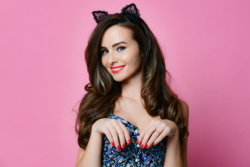 Young female with red lips with make up wears retro style cat ears modern pink background pinup girl
