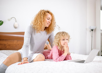 Mother and daughter browsing the net together. close up side view photo. leisure activity