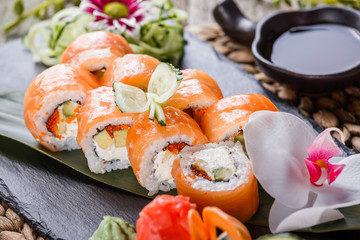 Sushi rolls set with salmon, cream cheese, red caviar, avocado and wasabi on black stone on bamboo mat, selective focus. Japanese cuisine
