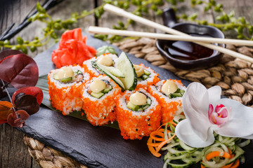 Sushi Roll - Maki Sushi made of Salmon, Red caviar, cucumber, avocado and cream cheese on black stone on bamboo mat decorated with flowers. Japanese cuisine