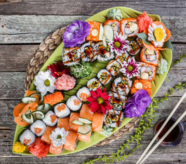 Sushi Set nigiri and sushi rolls decorated with flowers on bamboo background. Japanese cuisine. Top view