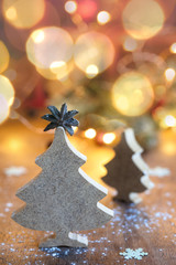 Two small wooden Christmas trees with festive light on background, vertical composition