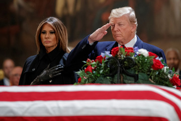 US President Donald J. Trump, with First Lady Melania Trump, salutes the casket containing the body of former US President George H.W. Bush in the Rotunda of the US Capitol in Washington