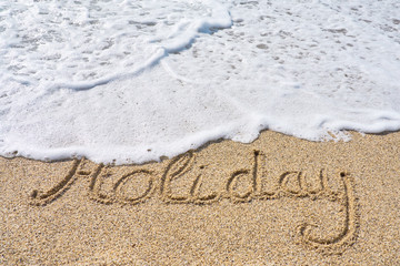 Holiday inscription on a tropical sandy beach with waves and foam on a background.