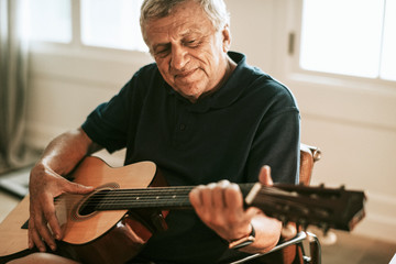 Senior man playing on his guitar Wall mural