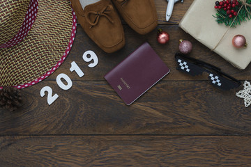 Table top view of Merry Christmas decorations & Happy new year 2019 ornaments concept.Flat lay essential difference objects to travel text & gift box with clothing  on modern wooden brown background.