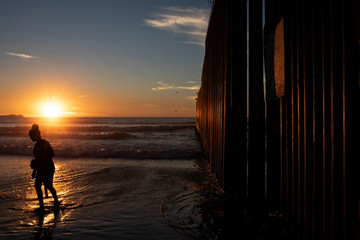 A woman is silhouetted during sunset next to the border wall on the beach of Tijuana