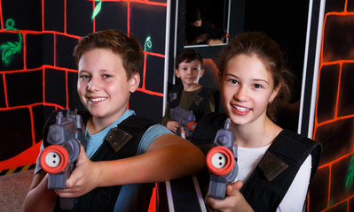 Girl and boy playing laser tag