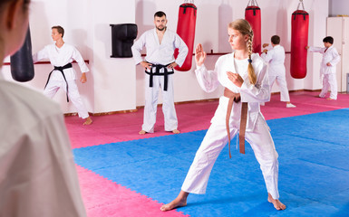 Tween girl mastering new taekwondo moves during group class with male coach