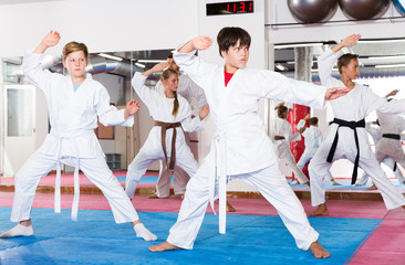 Kids exercising karate movements with trainer