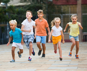 kids actively playing and running together on street on summer day