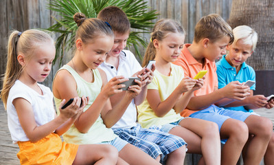 Busy children holding smartphones  and sitting