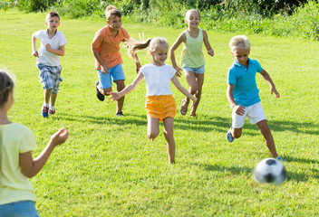 children playing football on meadow .