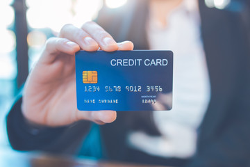 Business woman hand holds a blue credit card.