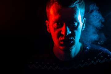 Portrait of a man who is angry and has bad emotions with a face mash and smoke around on a black isolated background. The face of the guy in the shade with color red and blue illumination.