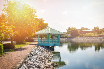garden park with pavilion on river side in sunny day / waterfront pavilion blue and pathway in the public park Wall mural