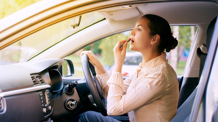 Woman using lipstick inside car. Urban background. Bad busy